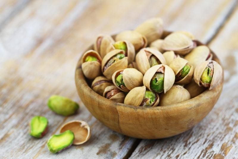 A wooden bowl containing pistachio nuts