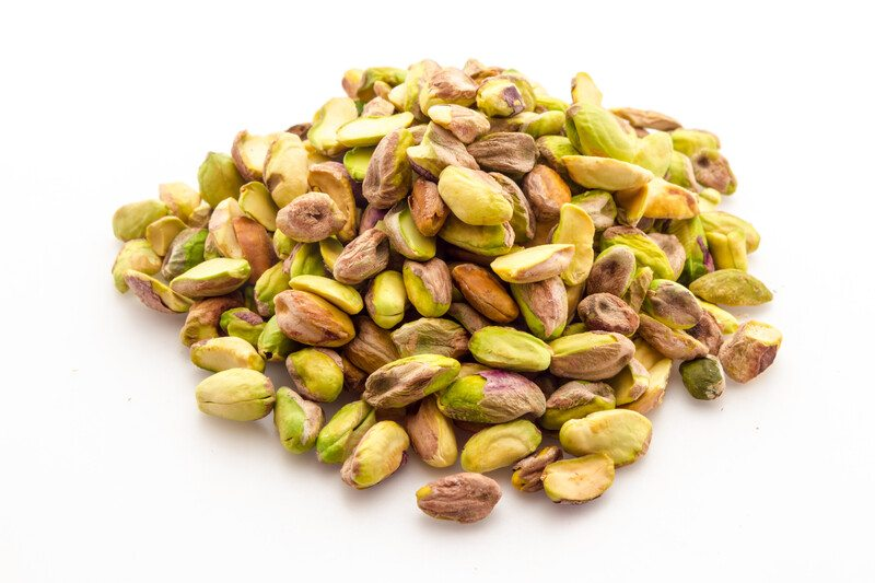 A pile of shelled pistachios rests against a white background.