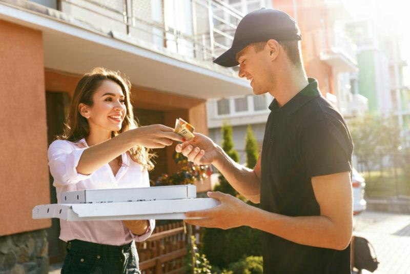 A young man delivering pizza to a woman