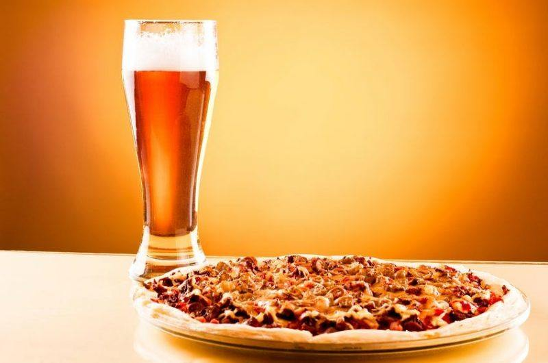 freshly baked pizza with a amber colored beer
