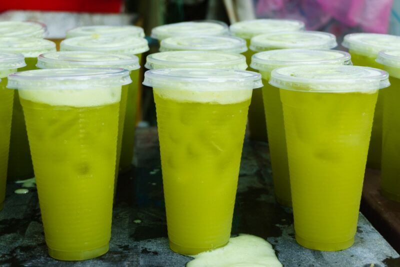Plastic cups with lids containing sugarcane juice and ice