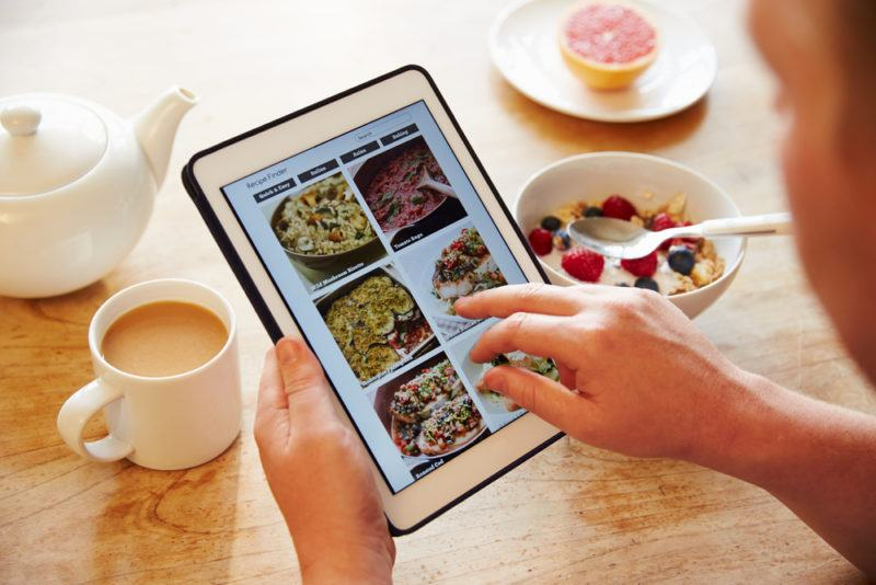 Cereal and coffee on a table, with a person selecting meals on a tablet