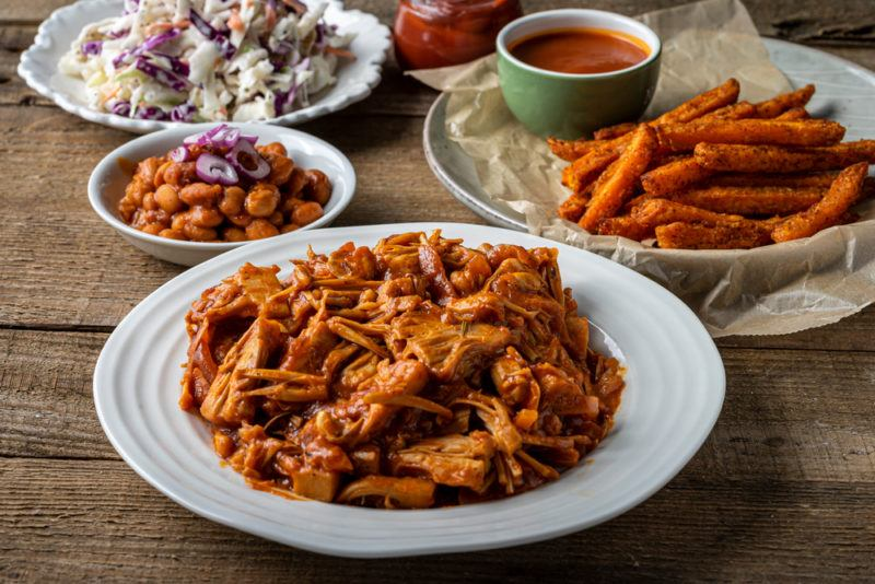 A plate of pulled pork alternative made from shredded jackfruit, with more bbq like foods in the background