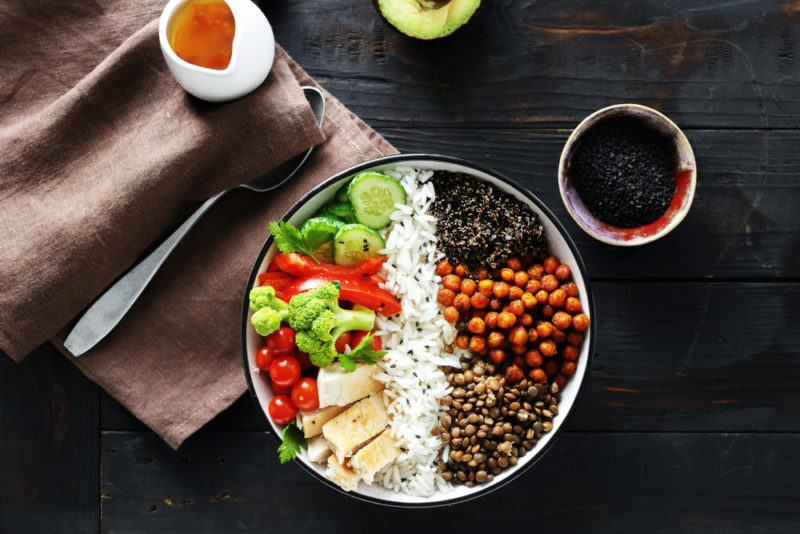 A bowl that is roughly split in half with rice down the middle and a selection of protein ingredients