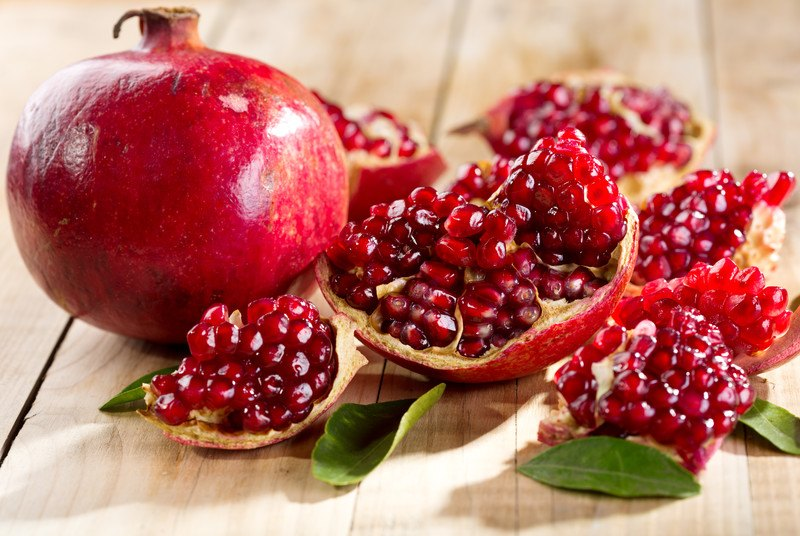 An open pomegranate fruit lies on a wooden countertop next to an unopened pomegranate fruit and some green leaves.