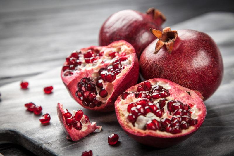Two pomegrantes on a table with another sliced pomegranate on a table