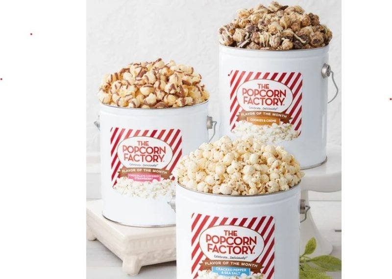 Three popcorn tin buckets featuring three varieties of popcorn; cracked pepper & sea salt, chocolate covered strawberry, and cookies and creme