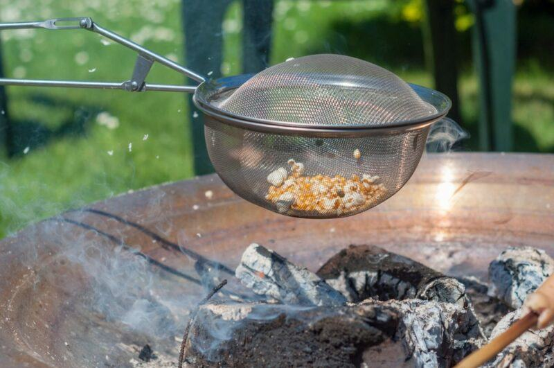 Someone holding a mesh basket over a fire to make popcorn