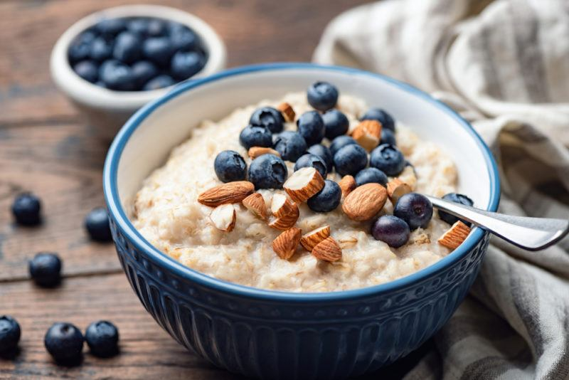 A blue bowl of porridge with blueberries and almonds