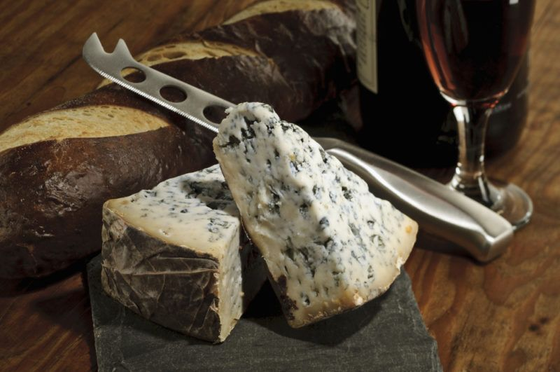 Blue cheese and bread on a board with a knife, next to a glass of port