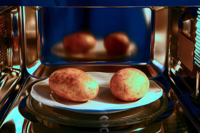 Two raw potatoes in the microwave ready to be cooked