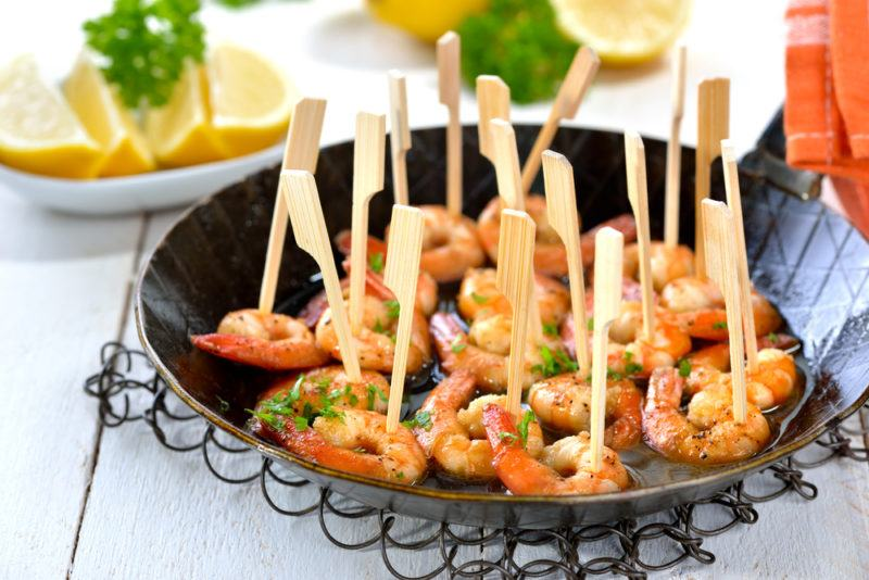 A black fry pan that contains prawns with cocktail sticks