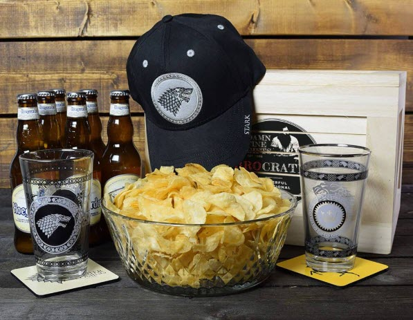 6 bottles of beer, 2 glasses on coasters, a crate with a hat resting on it and a bowl full of chips.