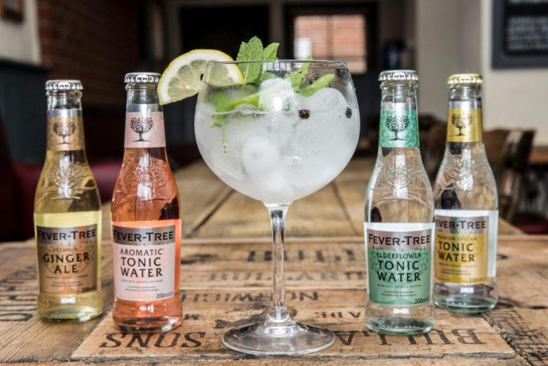 Four bottles of Fever Tree tonic water surrrounding a large glass of gin and tonic