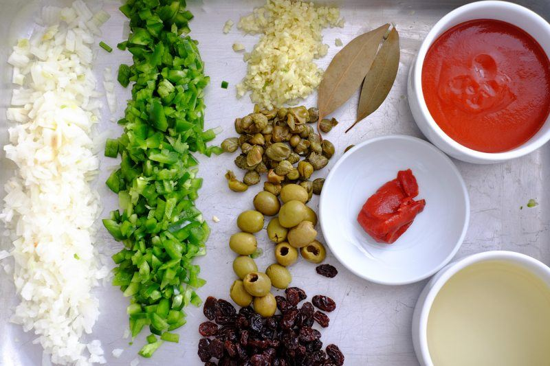 chopped onions, peppers, garlic, raisins, capers, bay leaves, tomato paste, tomato sauce, green olives