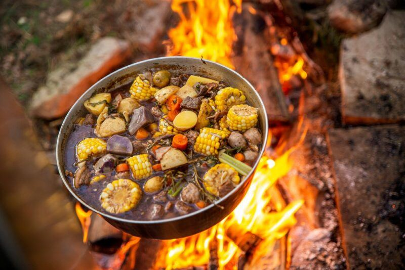 A pot over a campfire, being used to prepare a stew