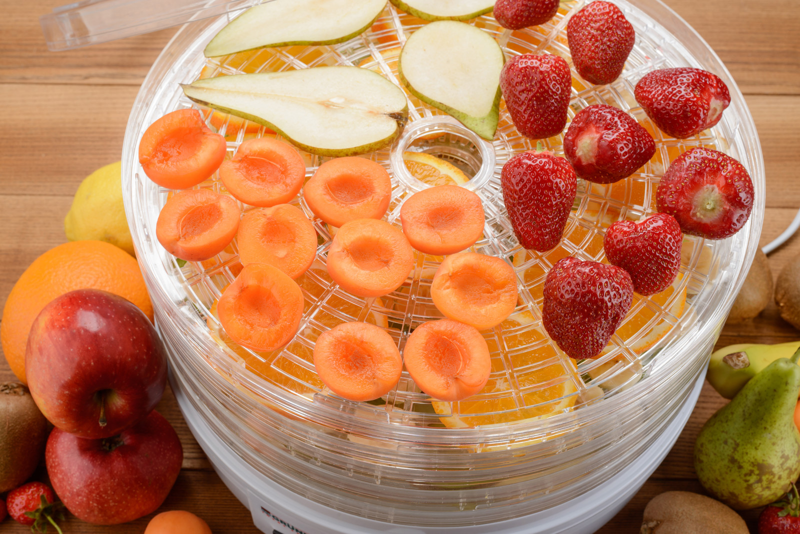 Process of drying fruits in a electronic multi-rack dehydrator. making tasty vegan snacks at home.