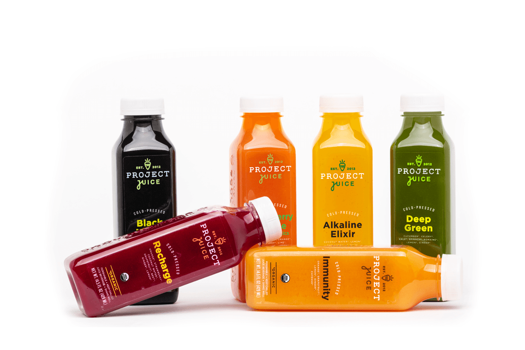 6 different colored bottles of juice 4 bottles standing upright and two on their sides.  The 6 bottles are of different colors, in the back from left to right black, orange, yellow, green, in the front Magenta and orange.