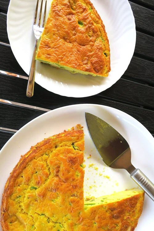 A bright quiche on a white plate with a piece cut out.