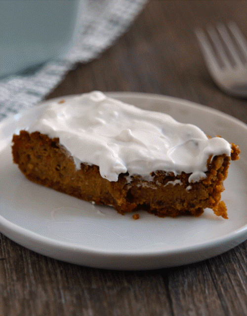 A small piece of pumpkin spice cake with icing on a white plate
