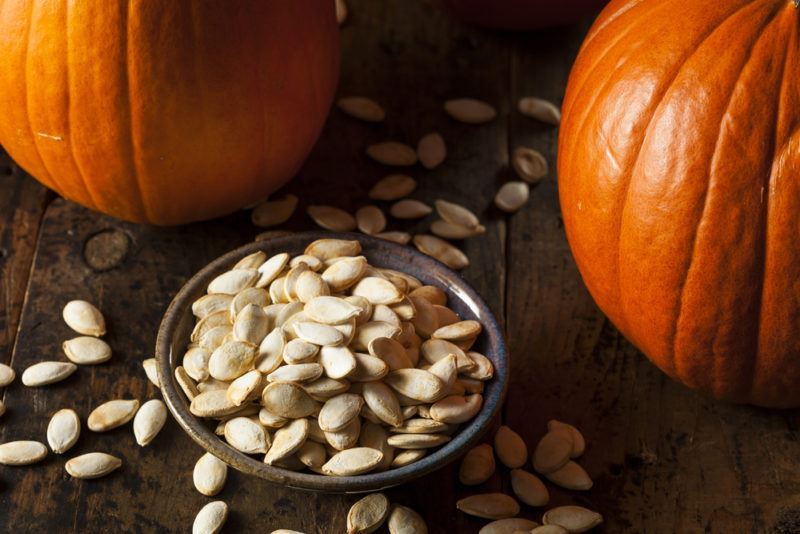 A bowl of unroasted pumpkin seeds, with pumpkin seeds scattered on the table and two orange pumpkins