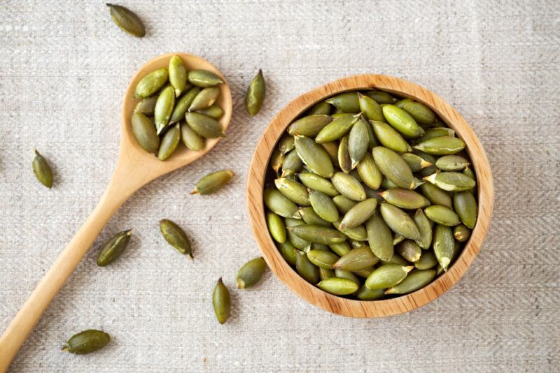 A wooden bowl and spoon with pumpkin seeds