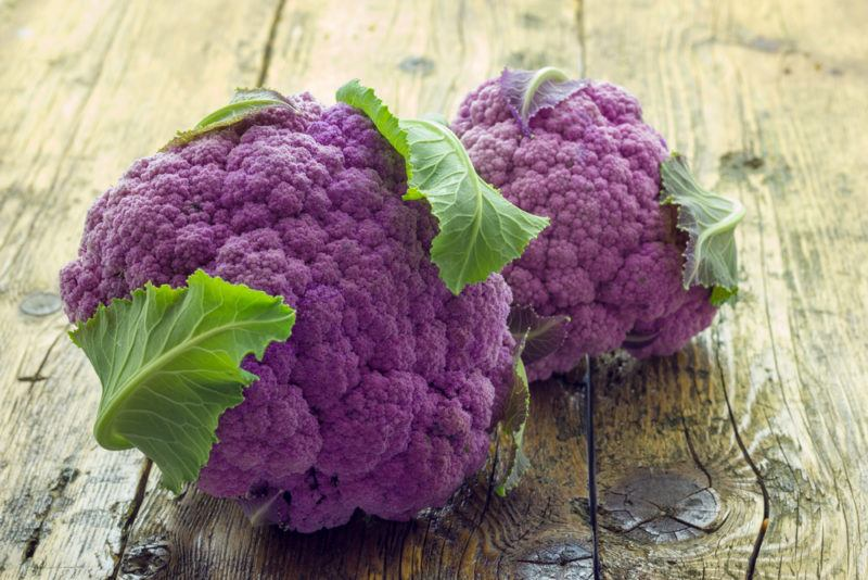 Two purple cauliflowers on a wooden table