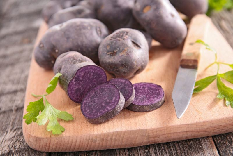 Purple potatoes on a cutting board with one of them being cut open.