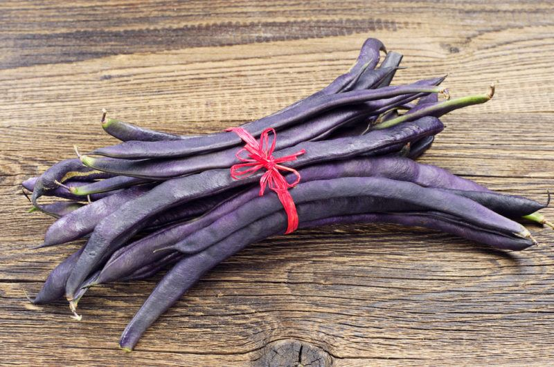 A bundle of purple string beans on a wooden table