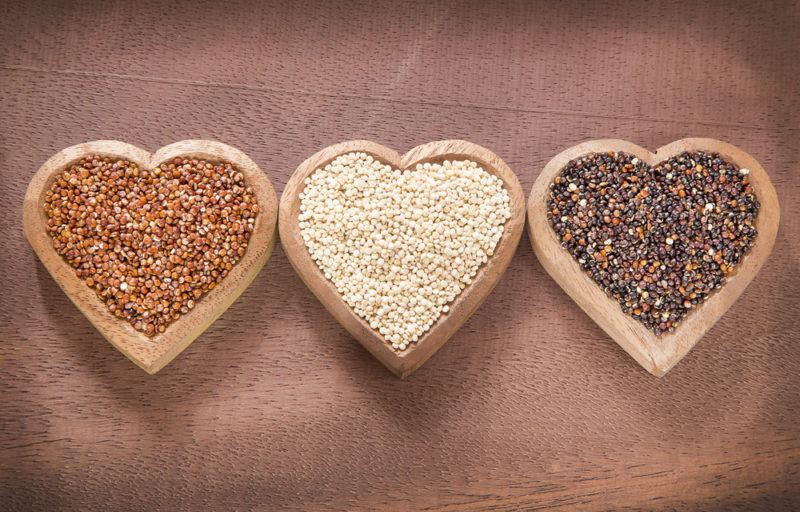 Three heart shaped bowls containing different colors of quinoa