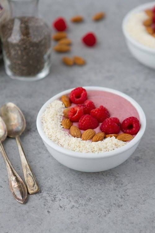 A white bowl with a pink smoothie and toppings like coconut and raspberries
