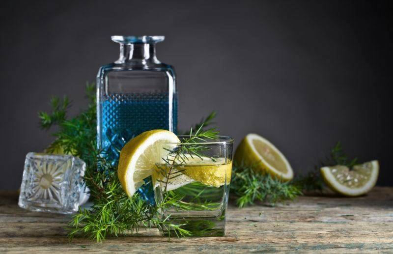 A bottle of blue gin with various garnishes, lemon wedges and glasses of gin and tonic