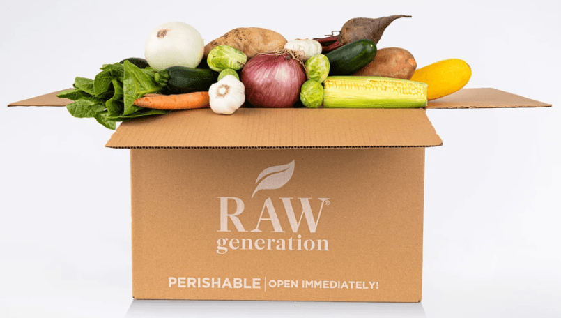 CARDBOARD BOX WITH RAW GENERATION STAMPED ON THE OUTSIDE OF THE BOX, THE BOX IS OVERFLOWING WITH VEGETABLES LIKE ONIONS, BEETS, BRUSSELS SPROUTS, CORN, AND GARLIC