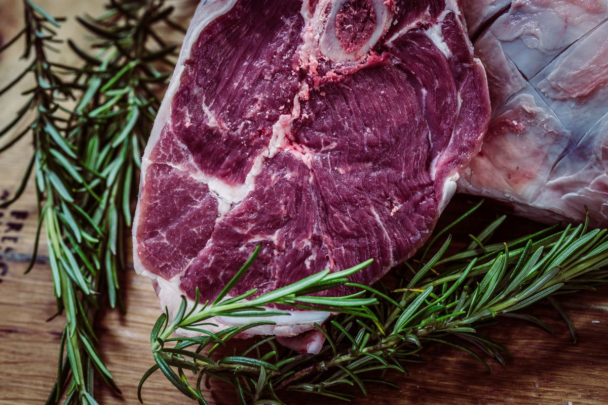 Exotic Meat of the Month Clubs -Raw Steak and fresh rosemary sitting on a wooden cutting board