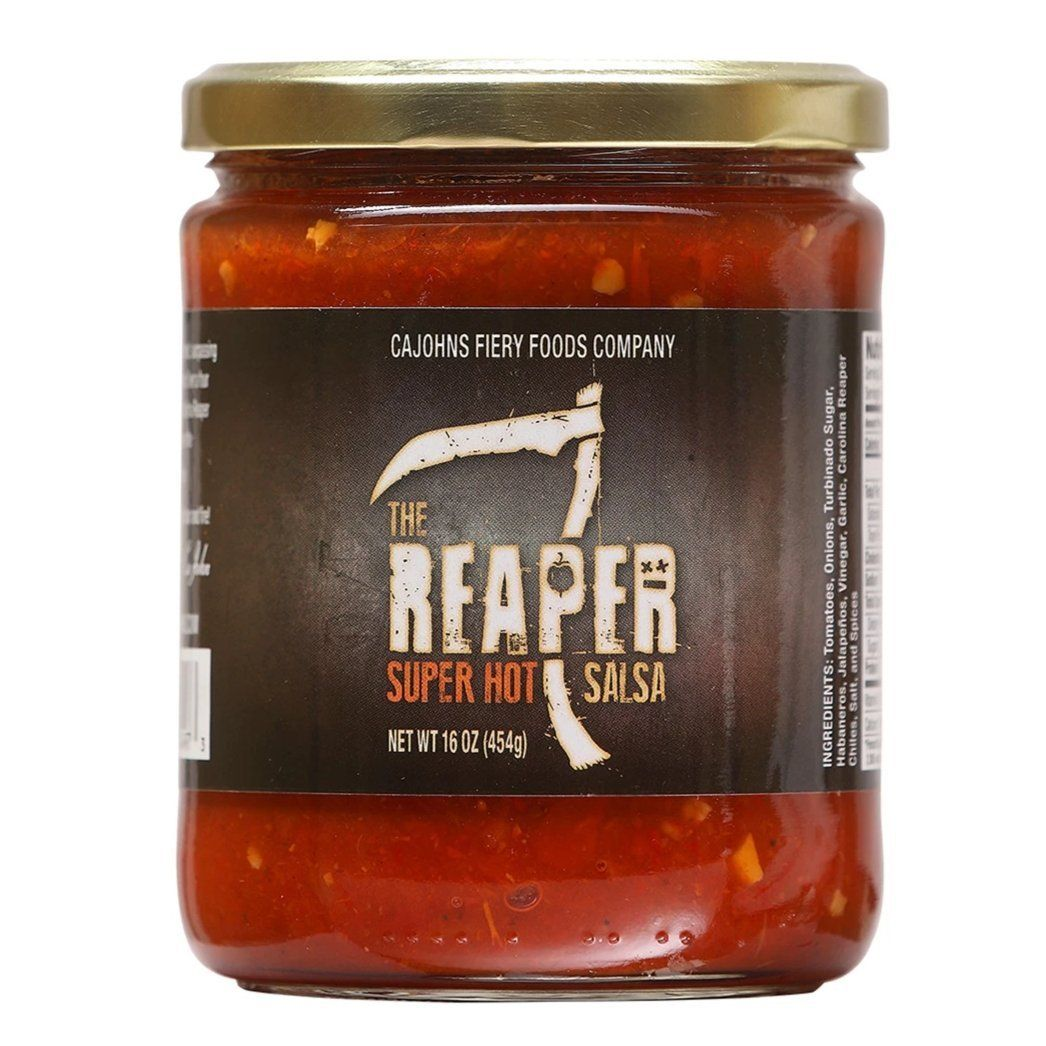 A 16 oz stout jar of salsa with a black label featuring a scythe and says from top to bottom - Cajones Fiery food company, The Reaper Super Hot Salsa