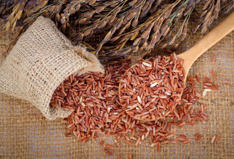 Red rice spilling out of a burlap bag and more red rice on a wooden spoon