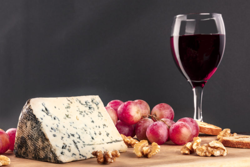 A tabletop with blue cheese, grapes, walnuts, and red wine