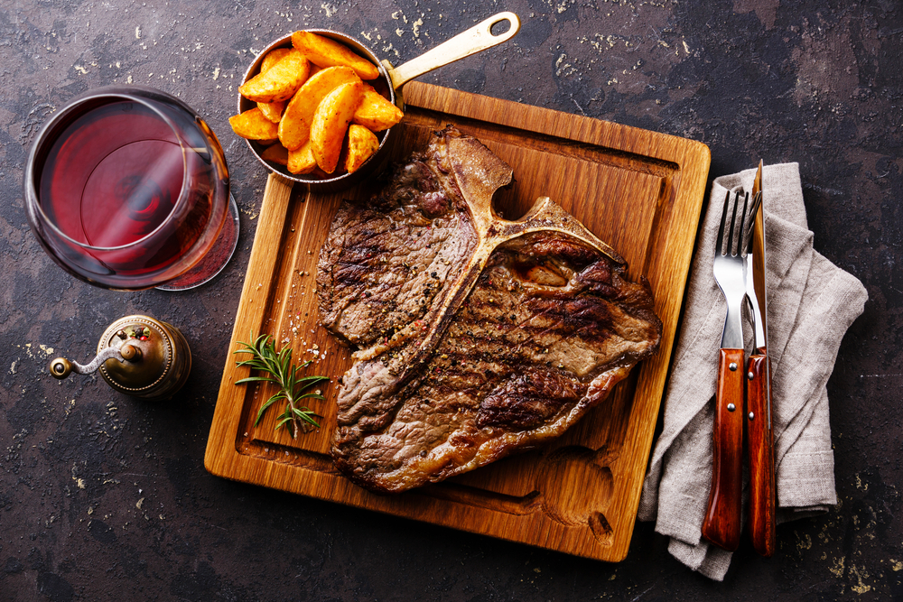 A square wooden board with a t-bone steak and fries, next to a knife, fork and glass of red wine