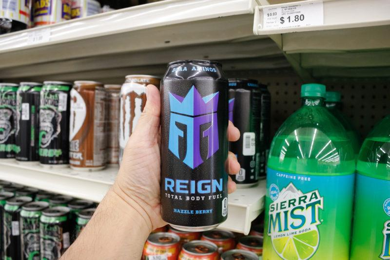 Someone holding a can of Reign Total Body Fuel in front of a grocery store shelf with other types of soda and energy drink