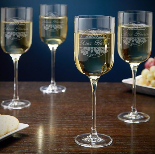 Four stemmed wine glasses with white wine