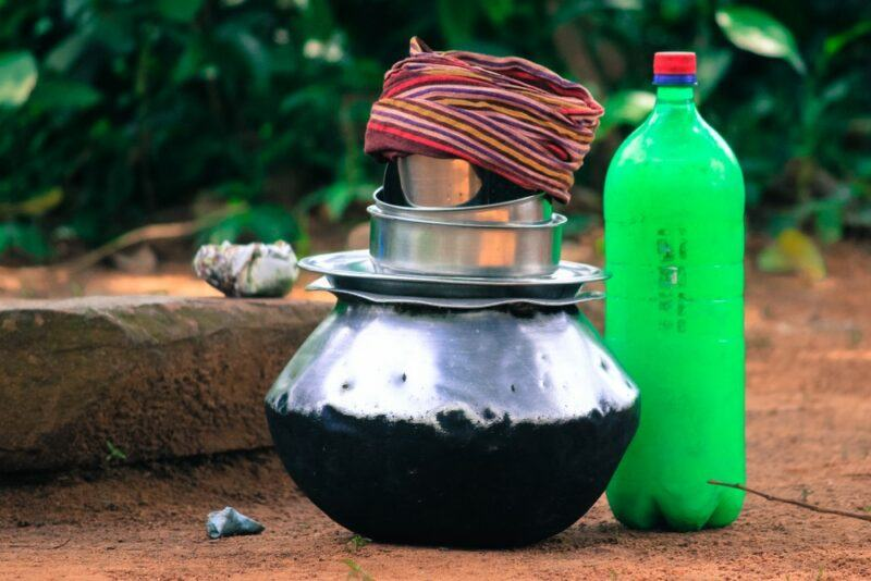 A green plastic bottle of rice beer next to a pot