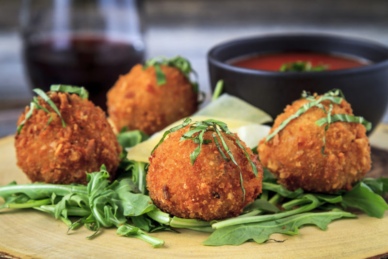 Fried risotto balls on a bed of microgreens, served with some marinara sauce.