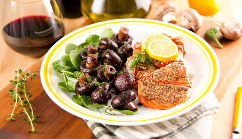 A white plate with yellow around the rim, containing roast salmon and cooked mushrooms, next to a stemless glass of pinot noir