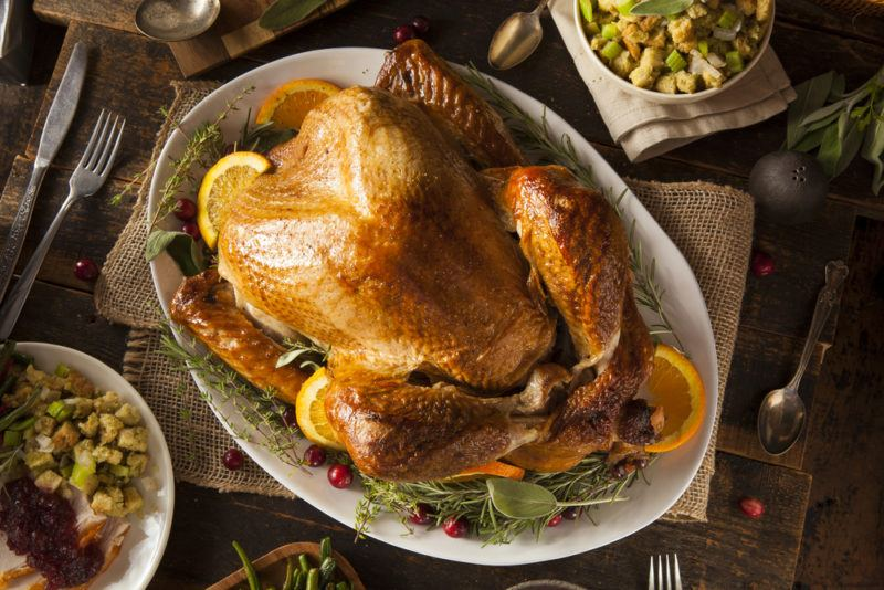 A roast turkey on a white plate, with a few lemons, and sides almost out of the shot