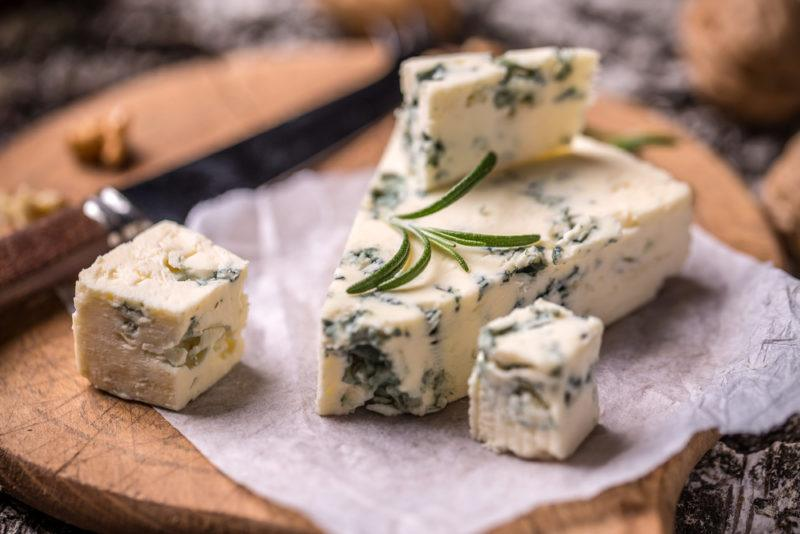 Roquefort cheese with walnuts on a wooden board