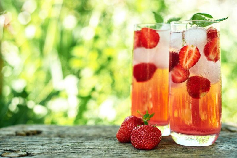 Two glasses of rose spritz with ice, strawberries and mint leaves