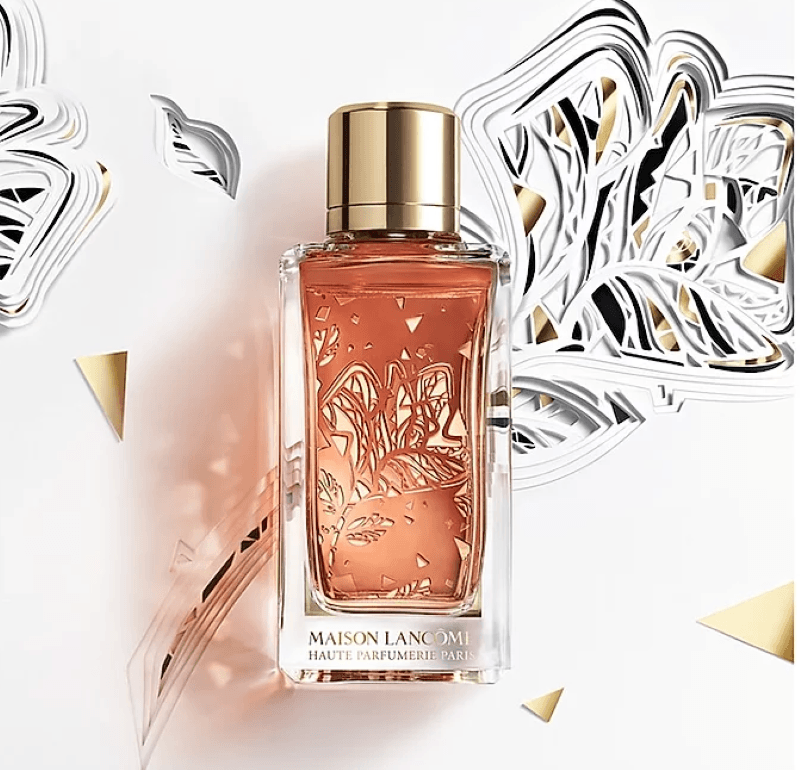 A Maison Lancome perfume bottle with pink liquid and gold cap.  In the background a white, gold, and silver flower and triangle design