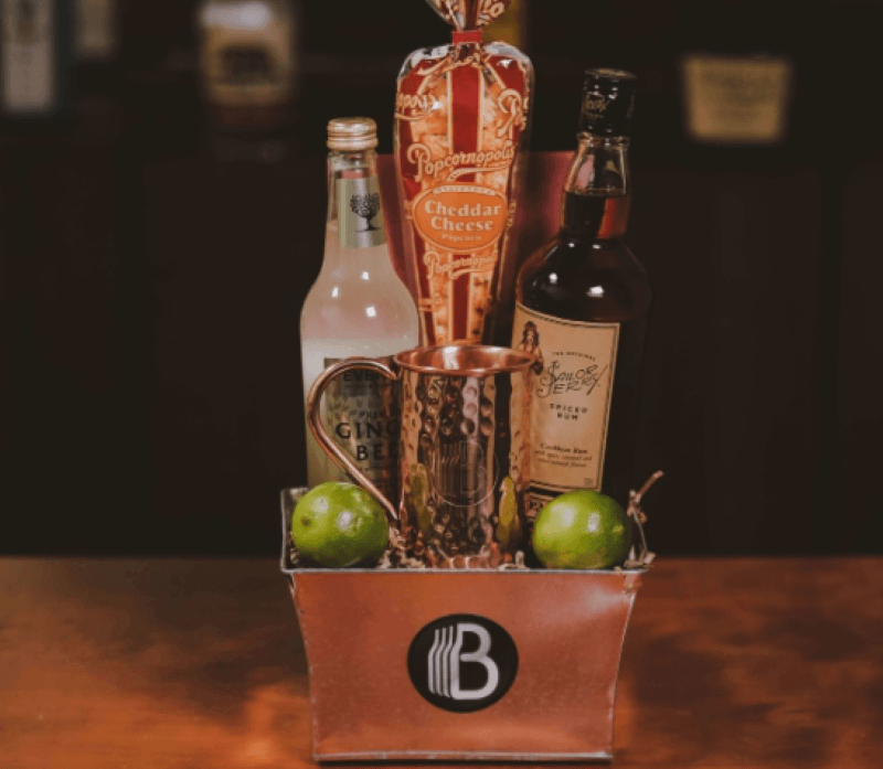Copper square basket with a hammered copper mule mug, with a lime sitting on either side and two in the upper left corner of the bakset is a bottle of ginger beer then a cone shaped bag of popcorn and on the right a bottle of rum.