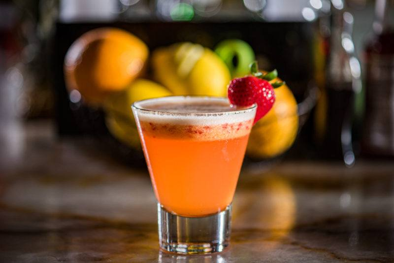 A rum runner cocktail in a short glass in front of a bowl of fruit