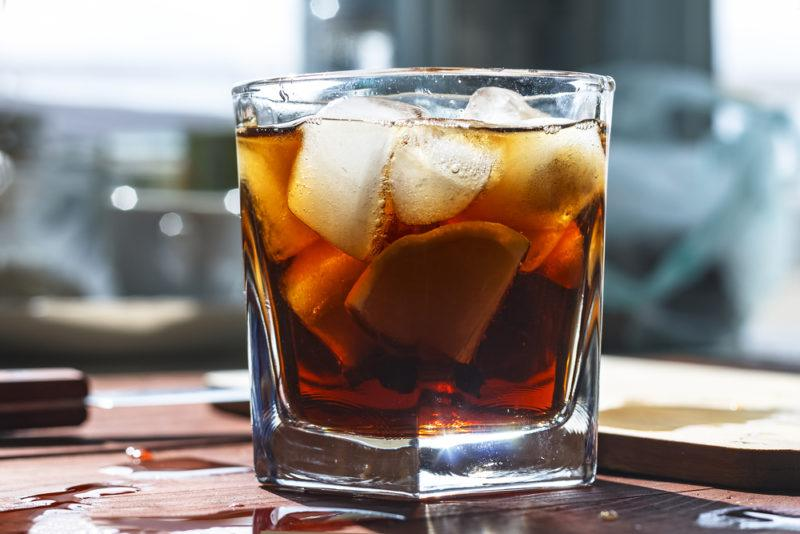 A glass with rum, coke and plenty of ice